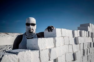 A man with scarf and goggles, leaning on a stack of bricks