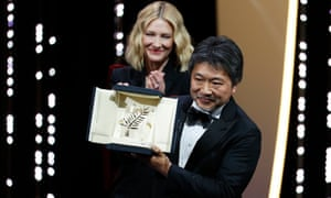 Hirokazu Kore-eda holds the Palme d'Or with jury president Cate Blanchett behind.