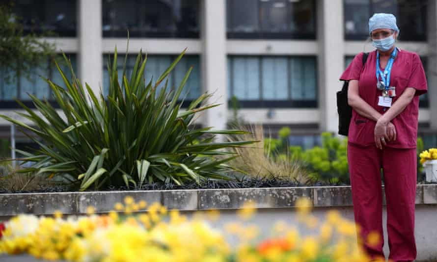 A healthcare worker pays her respects at St Thomas' hospital in London as part of a day of reflection to mark the anniversary of Britain's first lockdown