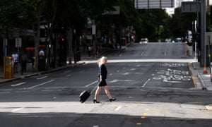A woman crosses an empty George Street during the morning peak hour in central Brisbane.