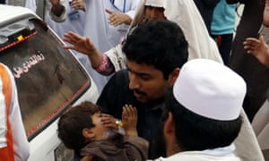 A man rushes a child to hospital in Peshawar, Pakistan.