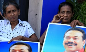 Sri Lankan President Mahinda Rajapaksa's supporters hold posters depicting their leader. The incumbent President is standing for a third term in office against one of his closest allies, Maithripala Sirisena.