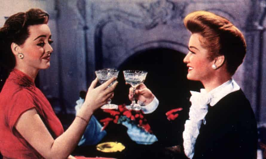 Bette Davis (left) and Miriam Hopkins toast each other in the 1943 film, Old Acquaintance.