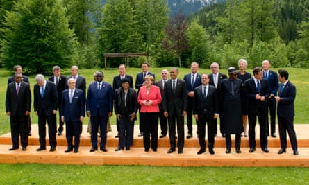 G7 leaders, including Angela Merkel (in pink jacket), and invitees line up for the traditional group photo at the end of the summit.