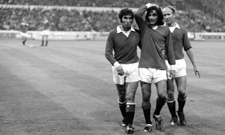 Tony Dunne helps George Best off the field against Chelsea at Stamford Bridge.