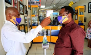 A man has his skin temperature checked in a shop in Harare, Zimbabwe.