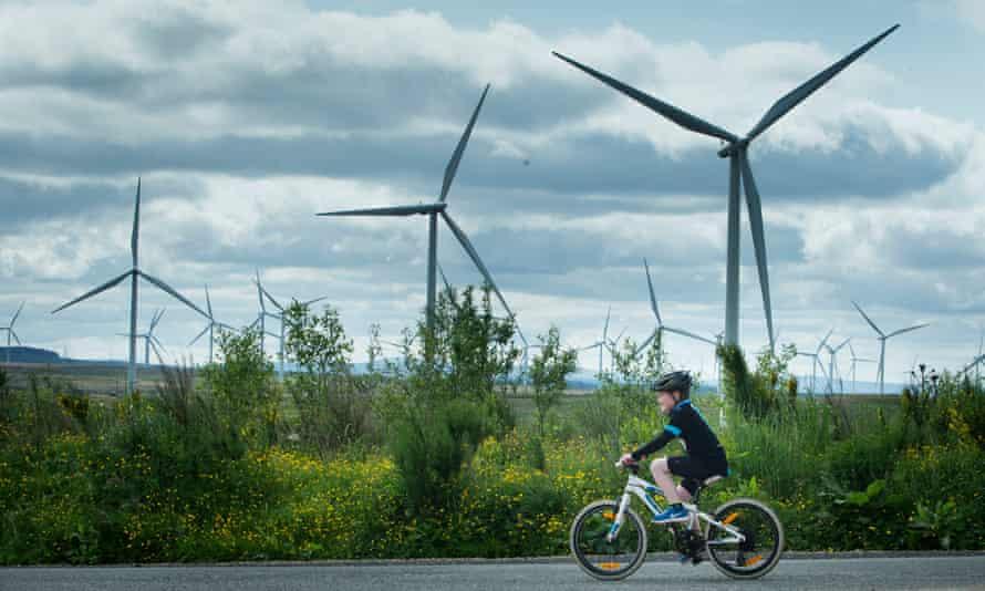 A child rides a bike past windfarms in Scotland