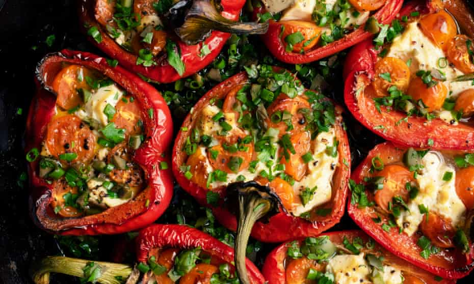 Baked red pepper halves, stuffed and with chopped herbs on top