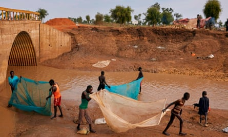 Residents of Yusuf Batir refugee camp fish together with the host community at a stream formed as a result of intense flooding in Maban, South Sudan in 2019.