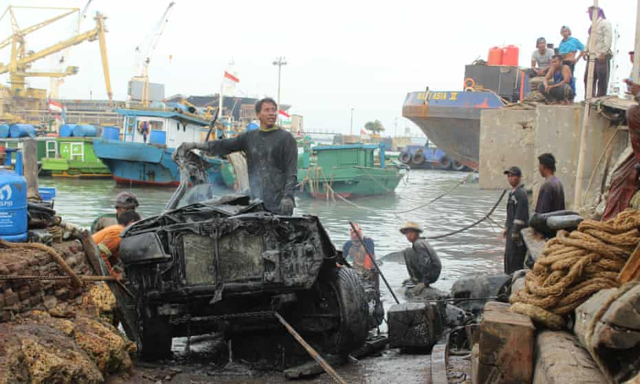 Traditional divers at Gresik disassembling a car they salvaged from the sea.
