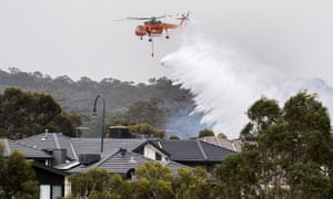 A skycrane drops water on a bushfire in scrub behind houses in the Melbourne suburb of Bundoora.