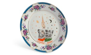 A porcelain commemorative plate showing Belka and Strelka looking sky- wards, with Saturn and Sputnik 5 picked out in gold.