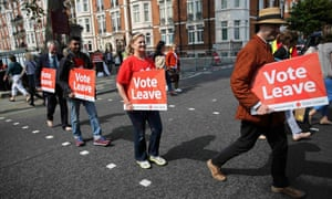 Vote Leave supporters holding banners cross the road outside the Chelsea flower show in London.