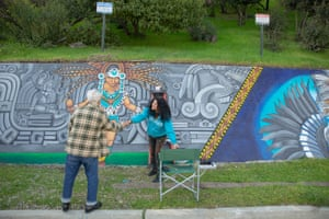 Pola Lopez helps to restore Daniel Cervantes' mural along the side of the Southwest Museum of the American Indian.