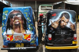 A mechanic stands between two tuk-tuk painted with graffiti portraits of musicians