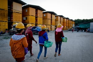 Female migrant workers return to their temporary homes after a day at the construction site