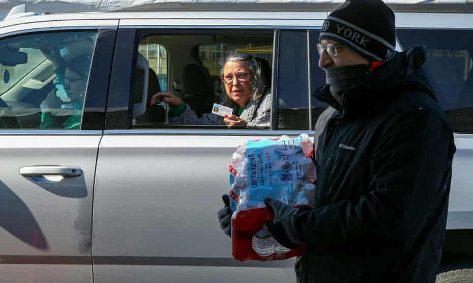 Volunteers distribute water tanks at the Schlitterbahn Waterpark parking lot in Galveston, Texas.