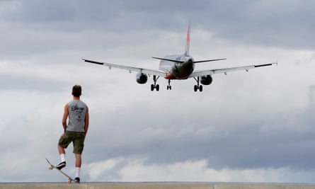 Man with skateboard watches plane take off