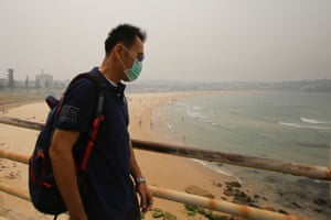 A man wears a mask as smoke haze from bushfires hangs over Bondi Beach
