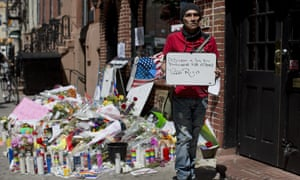 A man poses for a photo with a sign expressing support for victims and survivors of the Orlando nightclub shooting, outside the historic Stonewall Inn in New York.