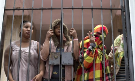 People stand behind a gate at the entrance of an abandoned residential apartment building in Flamengo neighborhood of Rio de Janeiro, Brazil. Squatters invaded the residence and demanded city officials put them into social housing.