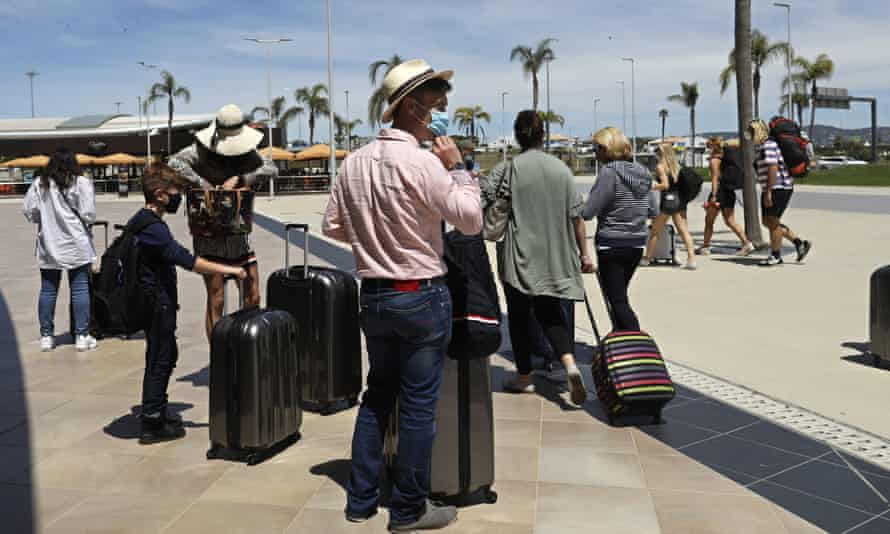 people queueing in sunshine at Faro airport in the Algarve, Portugal.