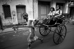 Young school children are whisked through the streets of Kolkata.