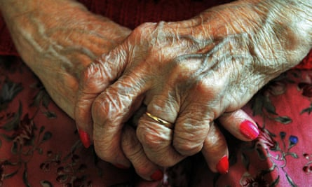 The clasped hands of an older woman