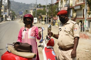 A commuter shows her identity card as police stop vehicles in Guwahati