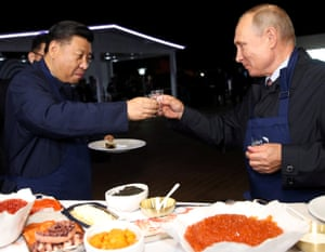 Russian President Vladimir Putin and Chinese President Xi Jinping share a toast during a visit to the Far East Street exhibition on the sidelines of the Eastern Economic Forum in Vladivostok, Russia