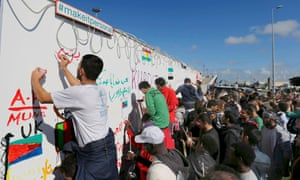 Migrants leave messages on a wall fresco in Calais. More than 3,000 people fleeing war and poverty in the Middle East, Africa and Asia now live in makeshift camps at the port.