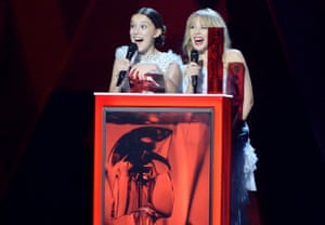 Millie Bobby Brown (L) and Kylie Minogue on stage