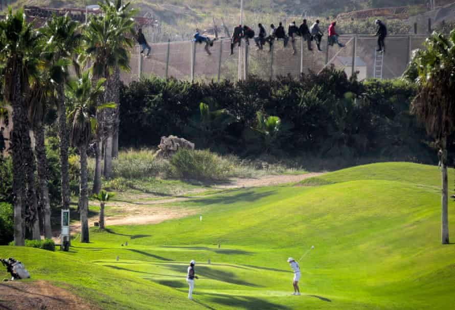 People try to cross into Spain's north African enclave of Melilla from Morocco in October 2014.