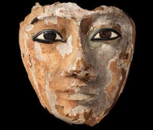 An Egyptian wooden face with inlaid eyes, originally part of a coffin.