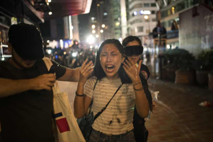 A woman reacts after being pepper-sprayed by police in Hong Kong, 20 October