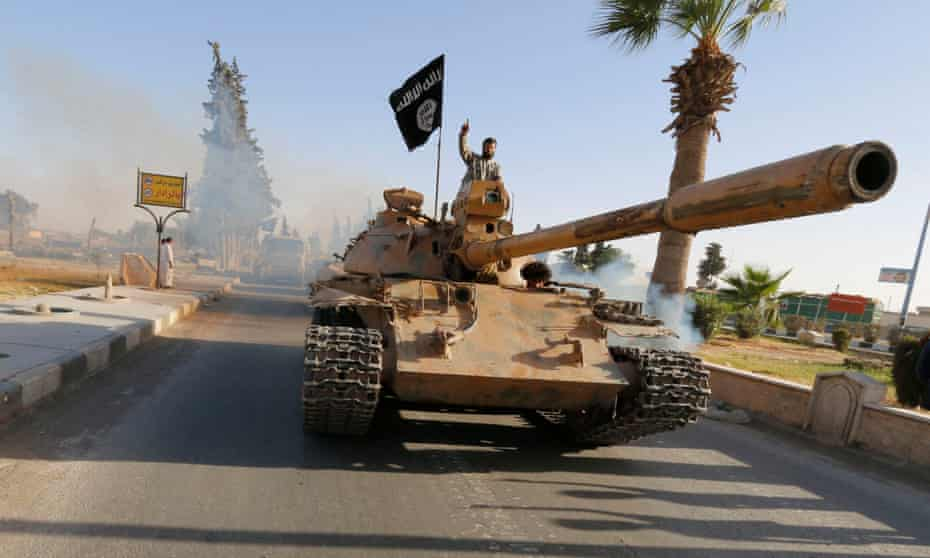 Militant Islamist fighters on a tank take part in a military parade along the streets of northern Raqqa