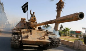 Militant Islamist fighters on a tank take part in a military parade along the streets of northern Raqqa province, Syria.