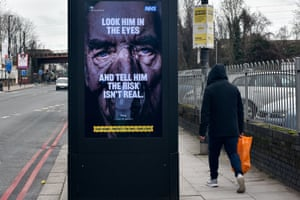 A government/NHS billboard on a London street shows a man on a ventilator and carries the message: 'Look him in the eyes and tell him the risk isn't real'