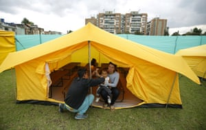 A Venezuelan migrant family inside a tent full of cots at the new camp in Bogotá
