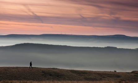 A man walking on Pendle hill in Lancashire at sunrise with low lying mist in the valley, UK.