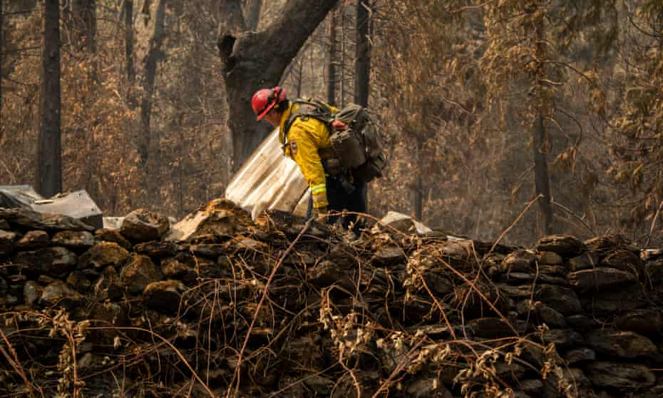 Fire Capt Chase Beckman inspects a structure destroyed by the Dixie fire, looking for clues about the construction, on Saturday.