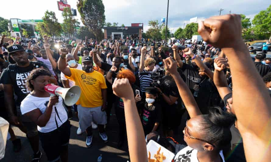 Protesters rally in the street in front of a Wendy's restaurant destroyed amid protests over the police shooting of Rayshard Brooks, whose death has been ruled a homicide.