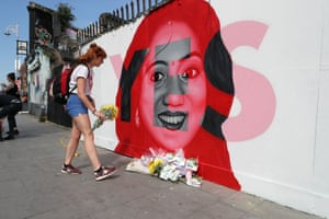 A woman in Dublin lays flowers next to an image of Savita Halappanavar, who died after pregnancy complications