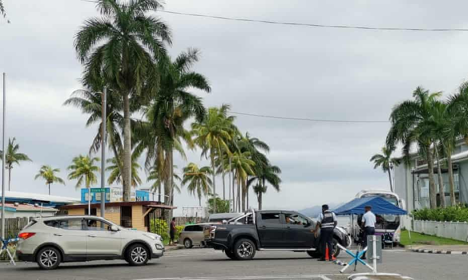 Police check cars at a checkpoint on a crossroad in Suva, Fiji. The government has imposed serious restrictions, including lockdowns and curfews, and police have made a large number of arrests.