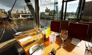 A set table next to a large window overlooking the river Ness