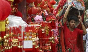 A lion dance walks performs near a shop selling Chinese New Year decorations in the Chinatown in Jakarta, Indonesia, 28 January. People of Chinese descent in the world's most populous Muslim country are preparing to celebrate the lunar New Year of the Pig on 5 February.