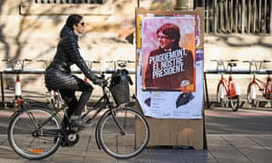 A cyclist passes a poster showing deposed Catalan president, Carles Puigdemont, ahead of Catalonia's regional election on Thursday.