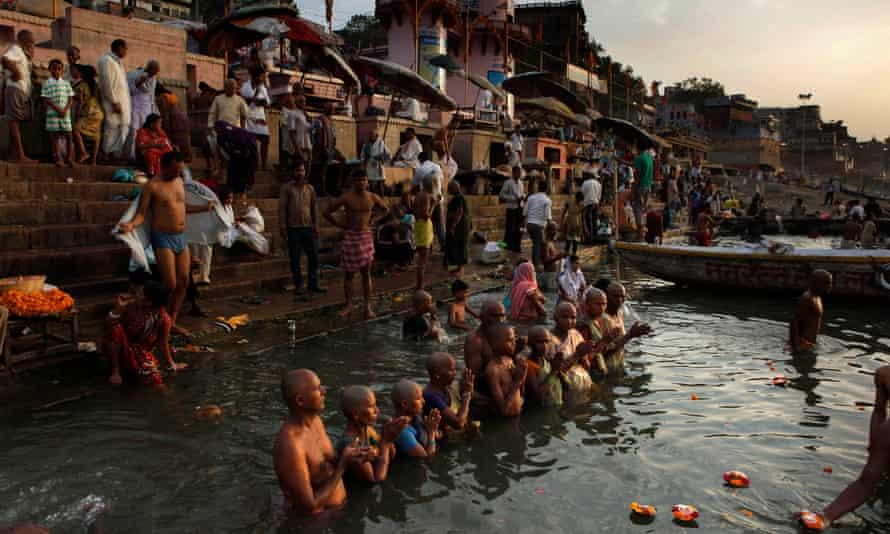 Hindu pilgrims in Varanasi gather for prayers and ritual bathing in the Ganges river.