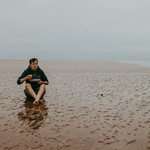 Author Patrick Barkham sat on a sandbank off the north Norfolk coast eating his lunch.