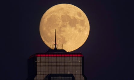 A nearly full moon rises, with an office building in the foreground